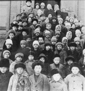 """Tervun kansakoululaisia. Kuvan ottamisaika ei ole selvillä, mutta taustalla oleva vuonna 1912 valmistunut puukoulu paloi ja sen tilalle rakennettiin sementistä """"Kurkijoen ylpeydeksikin"""" mainittu uusi koulu, jonka seinät ovat vieläkin pystyssä."""