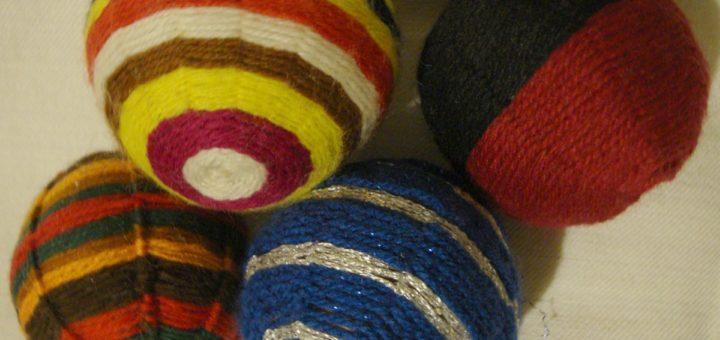 Erilaisia lankapalloja, joista suurin valkonapainen, on äidin tekemä opetuspallo, siinä on myös enemmän tukilankoja.