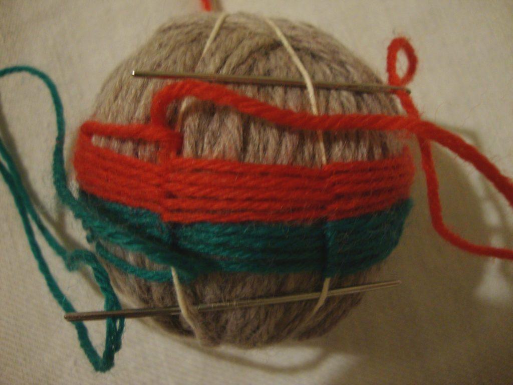 Lankapallon päällystys, sileänä pintana on punainen lanka ja kohotetut tukilangat on tehty vihreällä langalla.
