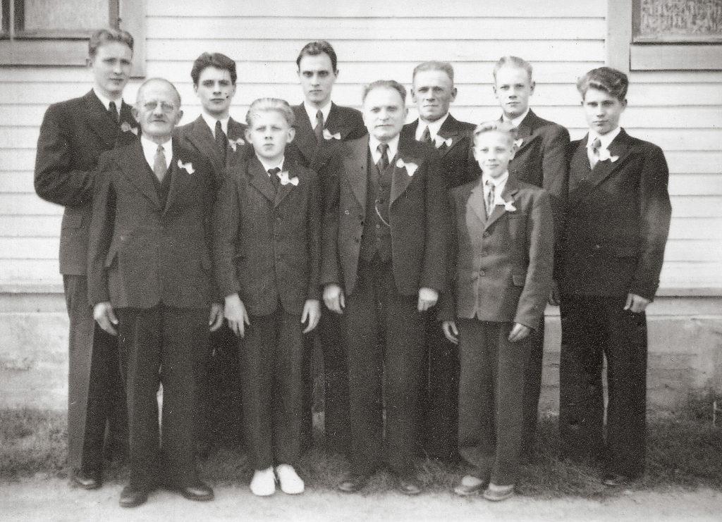 Mellilän torvisoittokunta 50-vuotisjuhlarusetit takinkauluksessa v. 1949. Kalevi Kuosa erottuu omien sanojensa mukaan ainoana evakkona halvemmalla jalkineratkaisullaan, sisaren valkoisilla kumitossuilla.