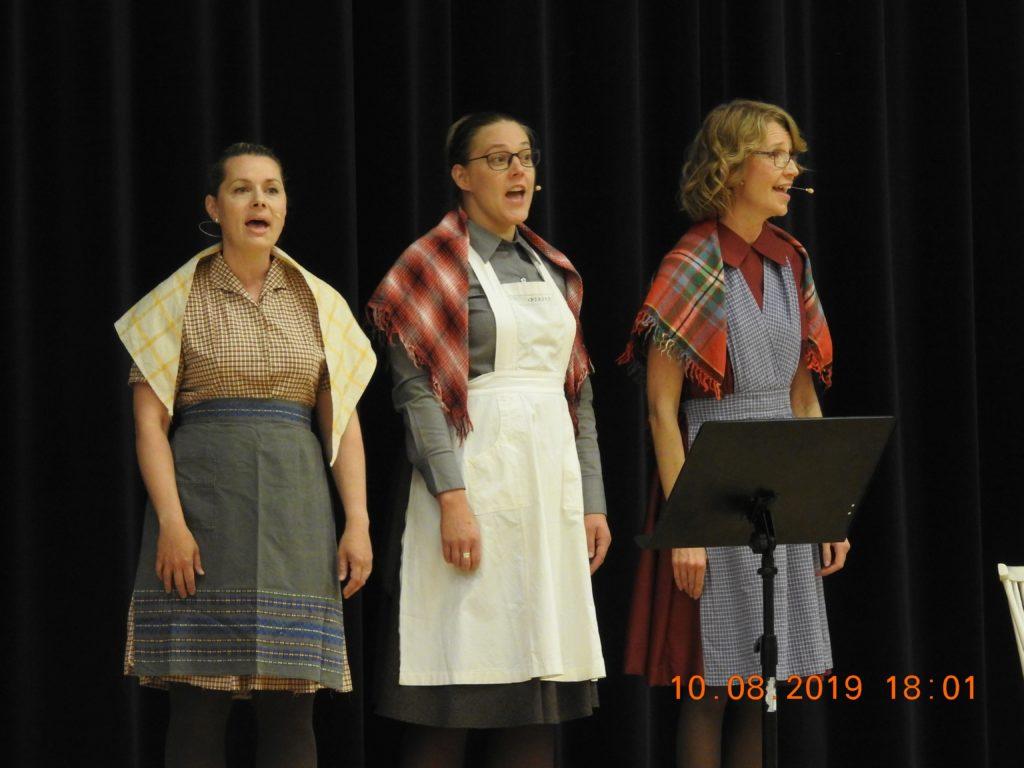 Ämmät äänessä: Laura Kilpiö, Elsa Hietala ja Iina Wahlström vetivät illan vauhdikkaasti. Laulut, vaatetus ja rytmi vaihtuivat. Kurkijokelaista luettiin, eikä sillä saanut sytyttää hellaan tulta.