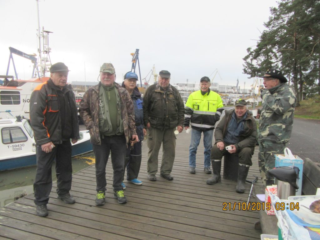 Kalakurkien pilkkipäivä oli totutusta poikkeava. Taustalla valmistuvat loistoristeilijät ja laiturista löytyy monenlaista venettä. Murkinakahveilla on hyvä aloittaa kisa.