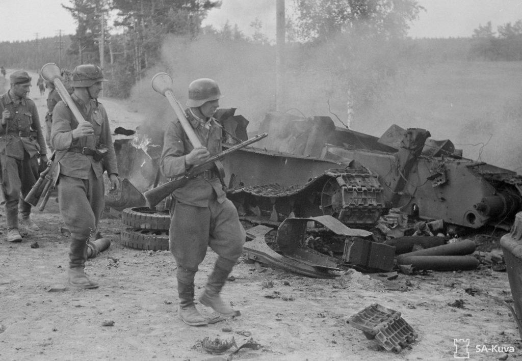 Suomalaiset sotilaat ohittavat panssarinyrkit olalla tuhotun venäläisen T 34-panssarin Ihantalassa 30.6.1944. Kuvan vaunun tuhosi saksalainen rynnäkkötykki Sturmgeschütz III. SA-kuva