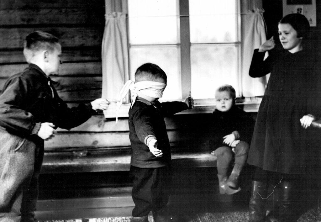 """Sokkosilla on yhä edelleen suosittu leikki. Ensimmäinen """"sokko"""" voidaan valita sopivalla lorulla. Kyytisen tuvassa Kurkijoen Särkijärvellä leikkivät vas. Lauri Kyytinen, Esa Asikainen, Martti Kyytinen ja Eila Asikainen. Kuva: Kurkijoki-museo/Pekka Kyytinen"""