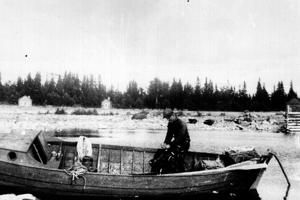 Korpisaarelainen kalastaja Martti Jakonen selvittelee verkkojaan Heinäsenmaan rannassa. Kurkijoki-museon arkisto