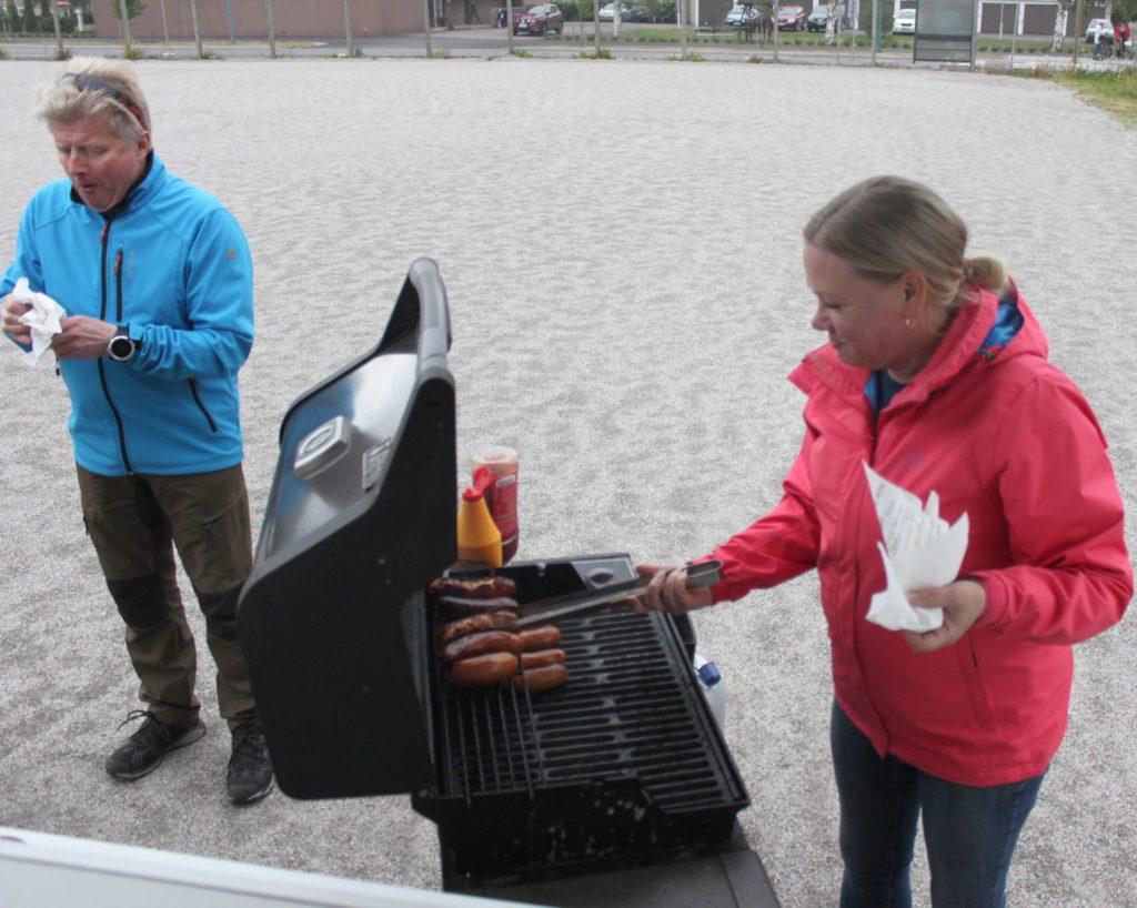 Makkarat paistuvat ja maistuvat kyykkäpelin lomassa kesällä 2019. Makkaran kuumuutta testaa Olli-Pekka Rastas.